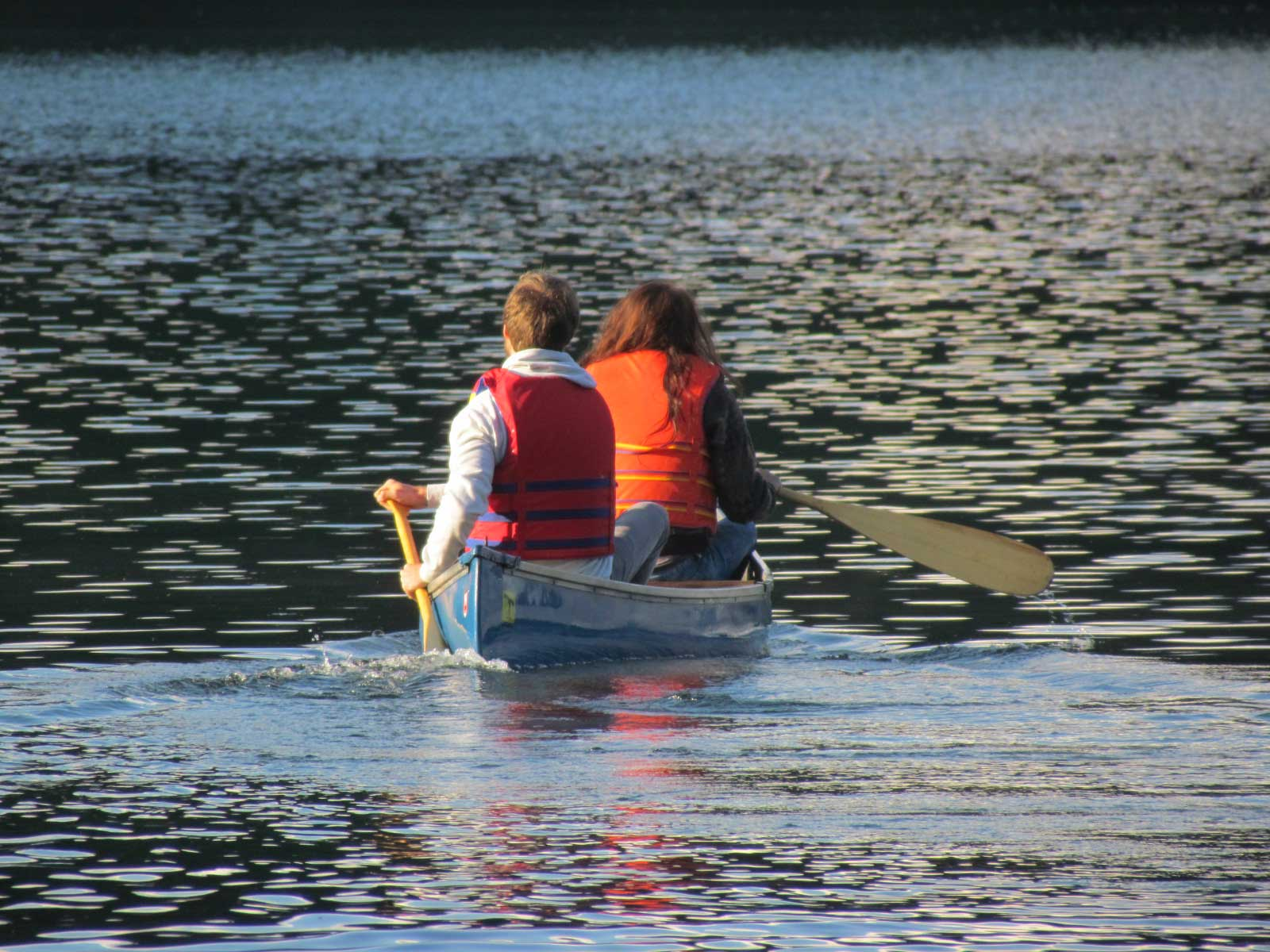 2 people canoeing on a lake - by Alex Galler